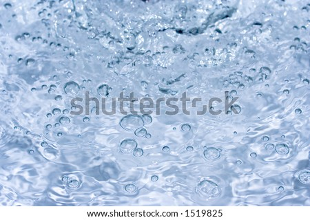 Close-up of bubbled water with soft blue/grey soft background freezed in motion