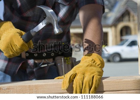 Close-up of builder's hands hammering a nail into wood