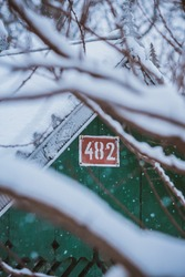 Close up of builing with street number during winter with blurry branches