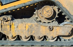 close up of bulldozer gears and track caked with mud