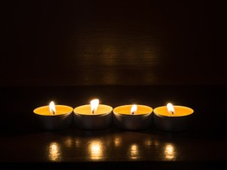 Close-up of burning candles on a wooden staircase. Coziness and warmth from a candle. Four candles are in a row. Side view. Dark background