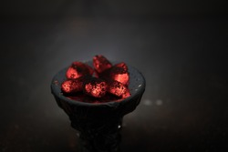 Close-up of burning charcoal cubes. Action. Cubes of embers burning in bowl for smoking hookah. Creative artwork decoration on dark background. Empty space. Selective focus