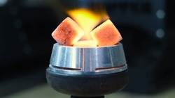 Close-up of burning embers on hookah. Media. Square red coals ignite when hookah is inflated. Red coals burn on hookah sup. Process of preparing shisha