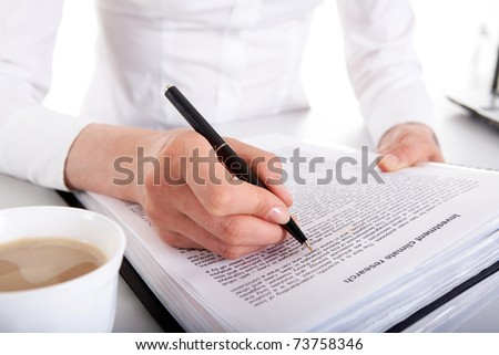 Close-up of business contract with female?s hands holding pen over it and cup of cappuccino near by