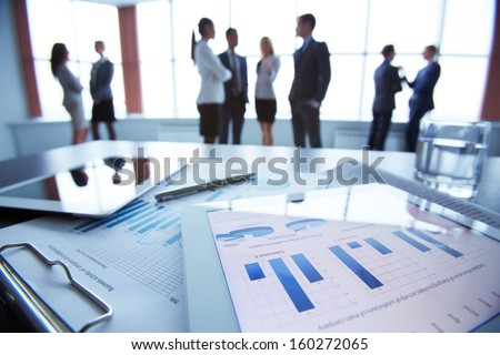 Close-up of business document in touchpad lying on the desk, office workers interacting in the background #160272065