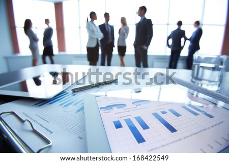 Close-up of business document in touchpad lying on the desk, office workers interacting in the background