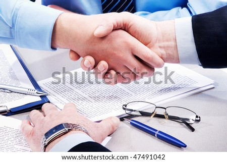 Close-up of business handshake over workplace with documents, pens, glasses