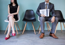 Close up of business man and business woman holding a blank and empty document paper waiting to be interviewed in the job recruitment processing