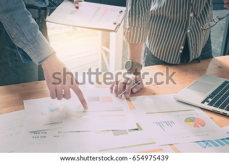 Close up of business man hand pointing at business document on financial paper during discussion at meeting. Group support concept. #654975439