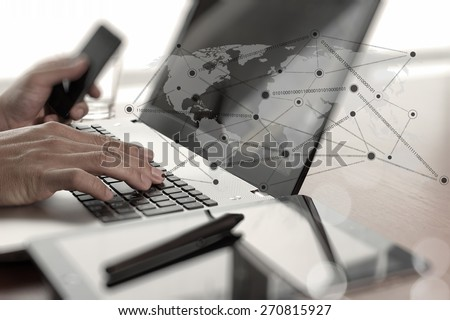 Close up of business man hand working on laptop computer with social network diagram on wooden desk as concept #270815927