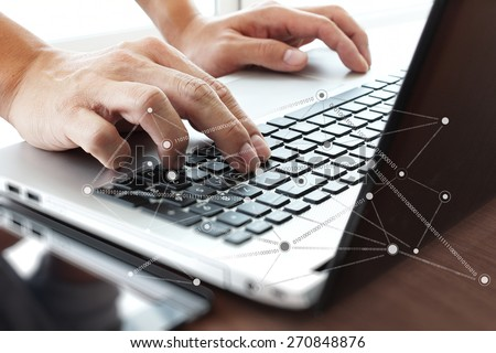 Close up of business man hand working on laptop computer with social network diagram on wooden desk as concept