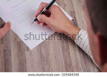 Close up Of Business Man Signing A Contract. Client signing credit agreement. Male hand signing papers. Lawyer, realtor.
