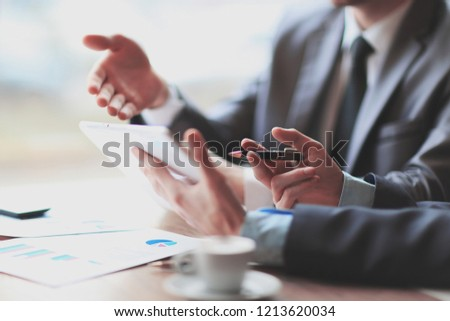 Close-up of business partners discussing document in touchpad