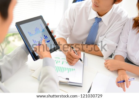 Close-up of business partners discussing financial document in touchpad