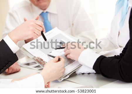 Close-up of business partners hands discussing new project at meeting
