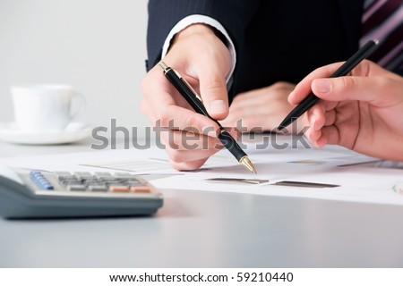 Close-up of business partners hands over papers discussing them