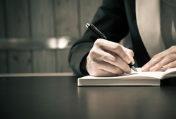Close up of business people hand in suit writing on notebook or document