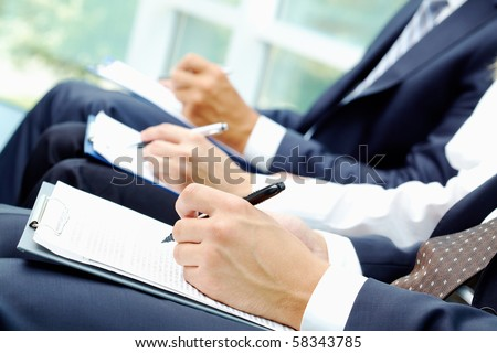 Close-up of business people hands with document writing at lecture