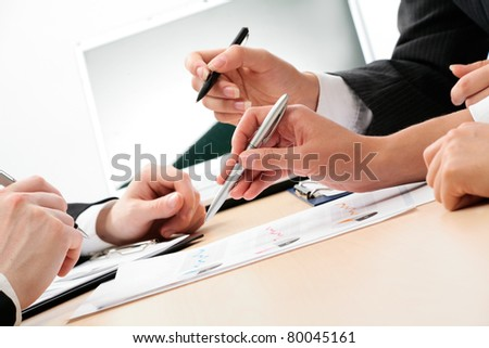 Close-up of business people hands with pen explaining a financial plan