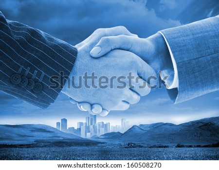 Close-up of business people handshaking on background of buildings and landscape