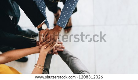 Close up of business people putting their hands together. Business colleagues showing unity.