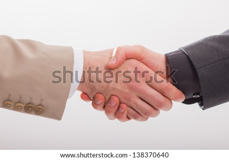 Close-up of business people`s arms handshaking. Isolated on white background.