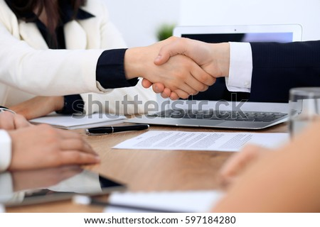 Close up of business people shaking hands at meeting or negotiation in the office. Partners are satisfied because signing contract #597184280