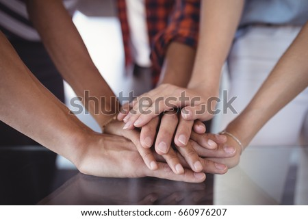 Close up of business people stacking hands on table in office