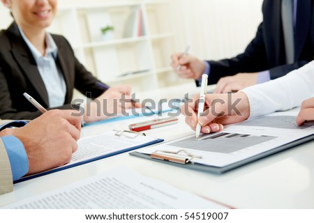 Close-up of business person hand over document in working environment