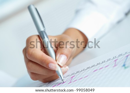 Close-up of business person hand with pen over paper