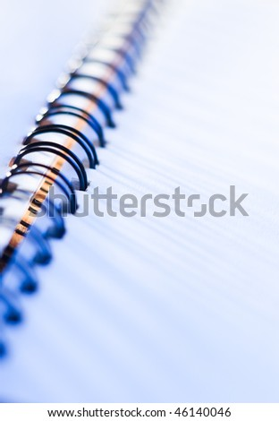close-up of business spiral notebook with a pen in blue light
