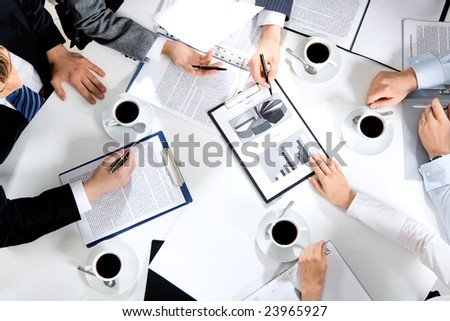 Close-up of business team sitting at the table and discussing a new project