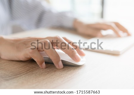 Close up of business woman hand typing on computer keyboard with the mouse while sitting working on the desk in the office or work from home Photo stock ©