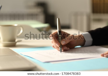 Close up of business woman hands filling out form at night in the office