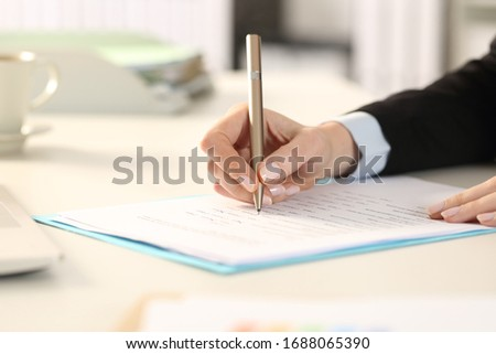 Close up of business woman hands filling out form sitting on a desk in the office