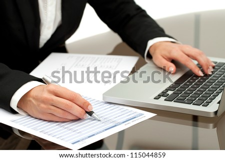 Close up of business woman's hands working on laptop and accounting documents.