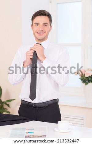 Close-up of businessman adjusting neck tie. waist up of handsome guy putting on neck tie