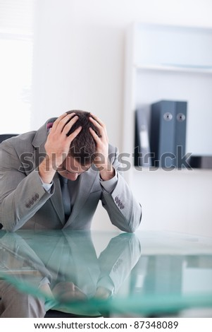 Close up of businessman after failed negotiation sitting behind a table
