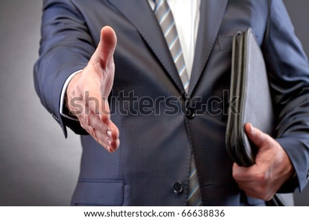 Close-up of businessman arm stretched for handshake