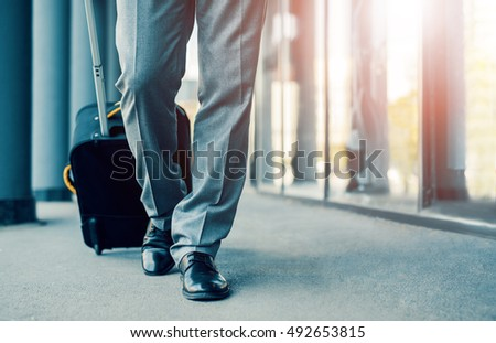 Close up of businessman carrying suitcase while walking through a passenger boarding bridge. #492653815