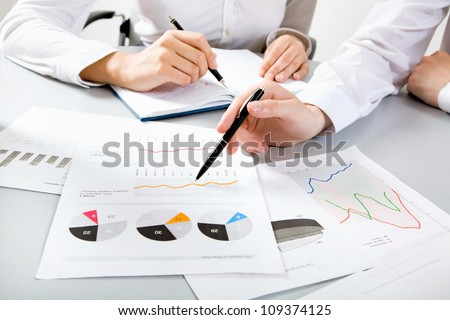 Close-up of businessman explaining a financial plan to colleagues at meeting