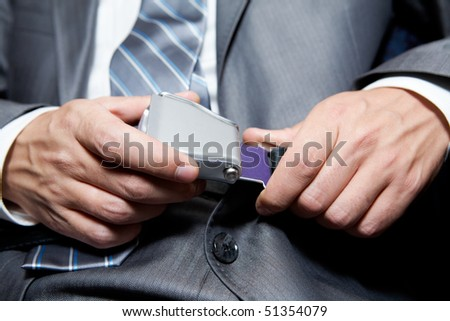 Close-up of businessman fastening security belt in airplane - stock photo