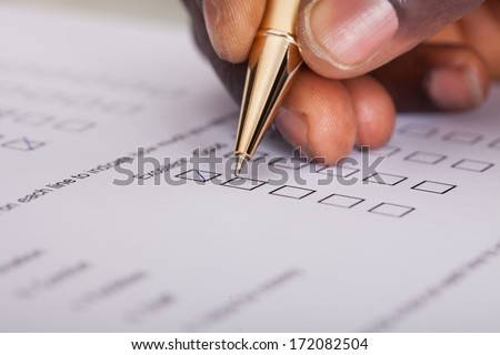 Close-up Of Businessman Filling Customer Survey Form #172082504