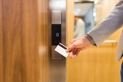 Close up of businessman hand holding key card to unlock elevator access, corporate building security concept.