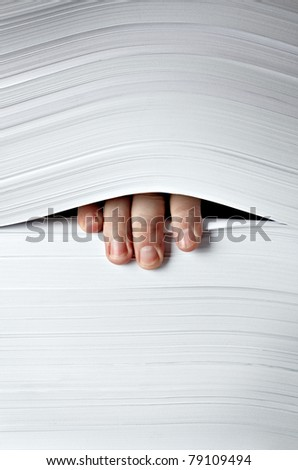 close up of businessman hand in stack of papers
