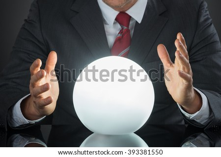 Close-up Of Businessman Hand On Crystal Ball On Desk #393381550