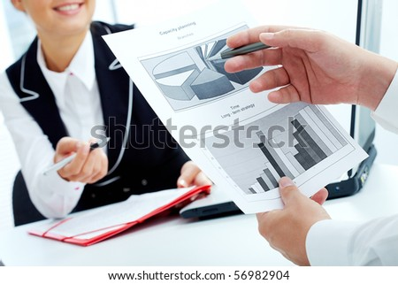 Close-up of businessman hand pointing at diagram while discussing documents with his colleague