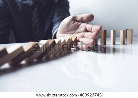 Close up of businessman hand stop dominoes continuous toppled vintage tone. #400923745