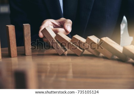 Close up of businessman hand Stopping Falling wooden Dominoes effect from continuous toppled or risk, strategy and successful intervention concept for business. #735105124