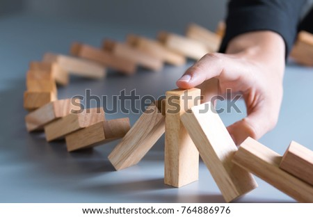 Close up of businessman hand Stopping Falling wooden Dominoes effect from continuous toppled or risk,  strategy and successful intervention concept for business.  #764886976